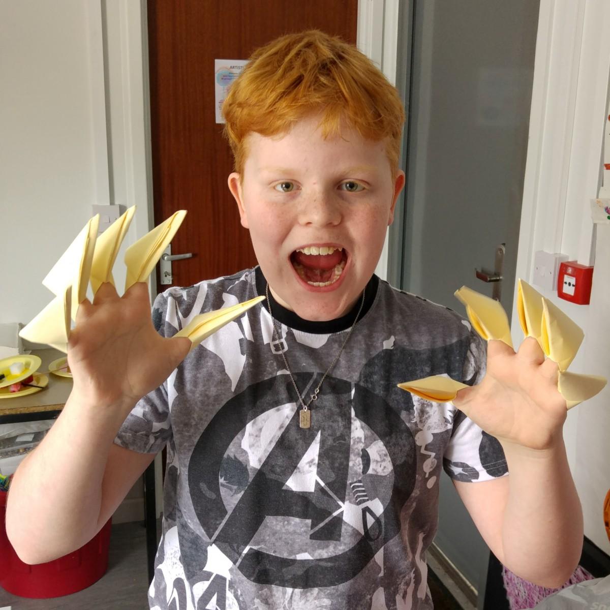 Boy wearing sharp paper nails